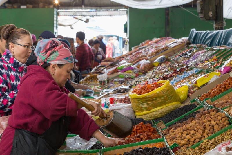 Vendedor secado de las frutas en el bazar de Osh foto de archivo libre de regalías