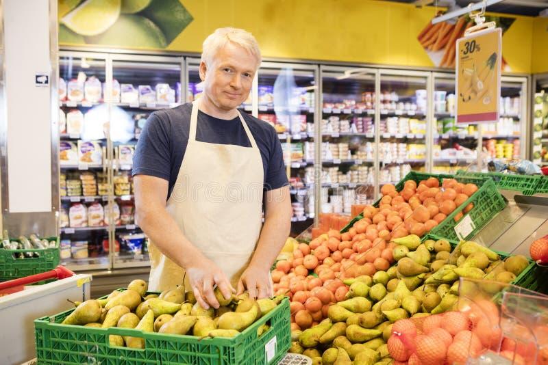 Vendedor seguro que arranja peras frescas no supermercado fotos de stock