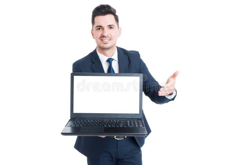 Vendedor sonriente alegre que muestra el ordenador portátil con la pantalla en blanco imagen de archivo libre de regalías