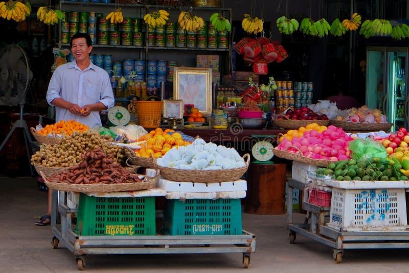 Vendedor sonriente de la fruta de la calle, cestas con las frutas tropicales, comercio de calle en Asia sudoriental fotos de archivo