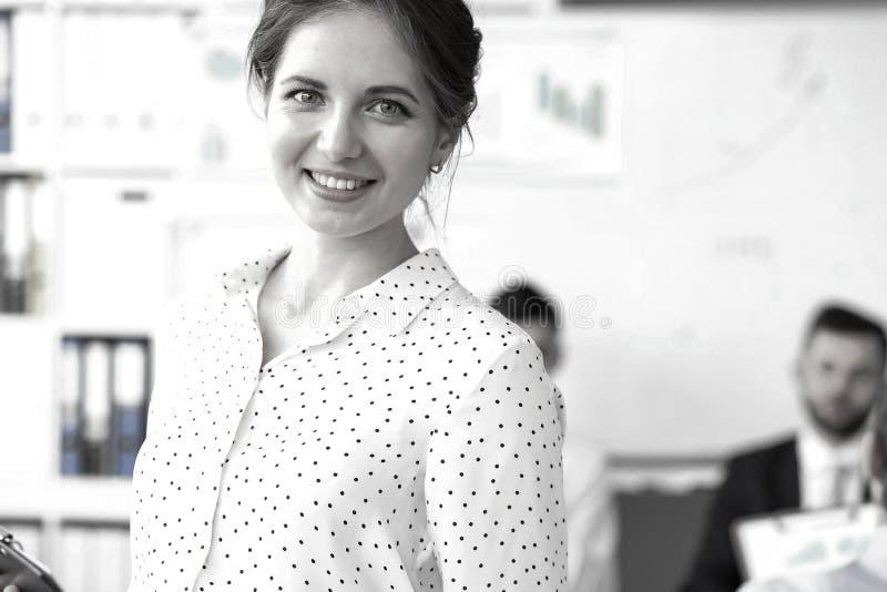 Vendedor sonriente hermoso joven en la oficina que mira in camera imagenes de archivo