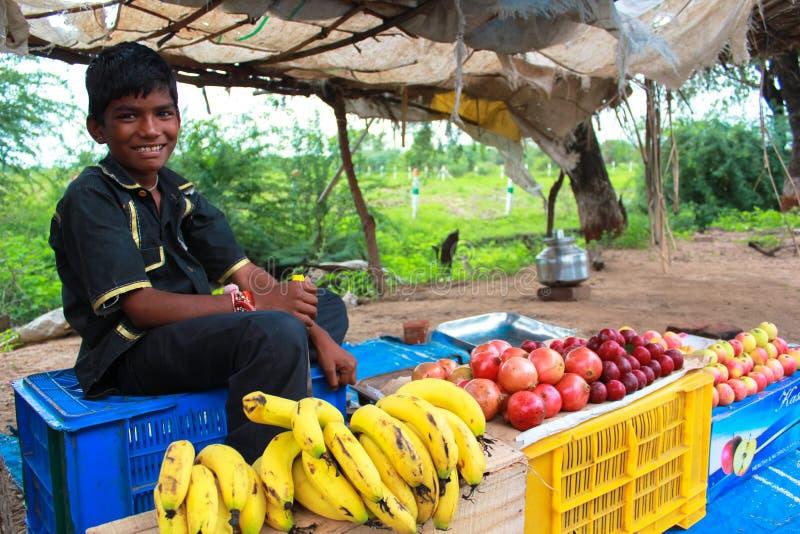 Vendedor sonriente joven de la fruta en las calles foto de archivo