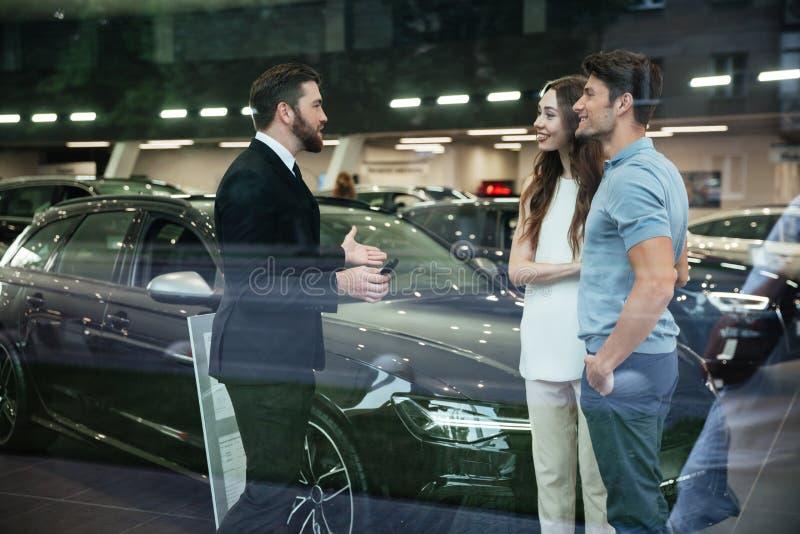 Vendedor sonriente que muestra el nuevo coche a un par en la sala de exposición foto de archivo libre de regalías