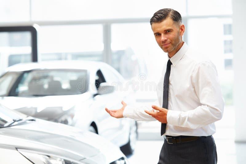 Vendedor Standing en la sala de exposición del coche y mostrar los nuevos coches foto de archivo