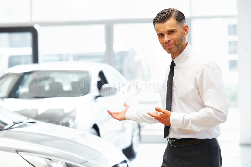 Vendedor Standing na sala de exposições do carro e mostrar carros novos foto de stock