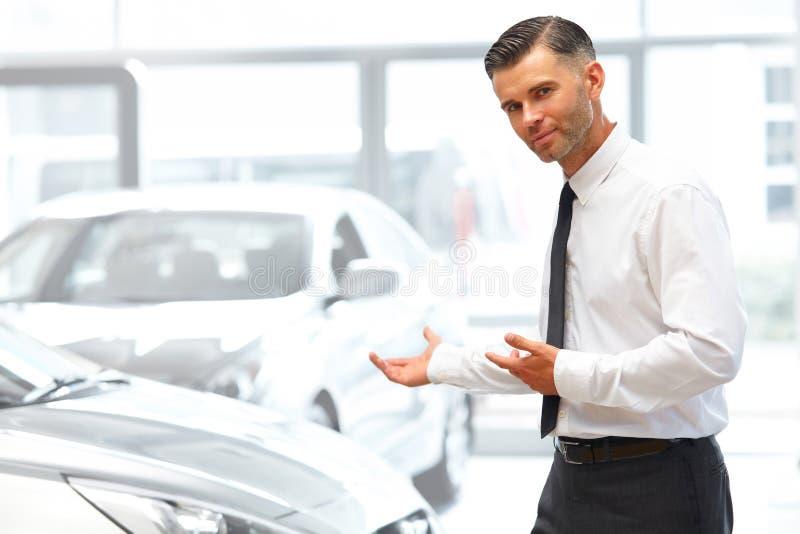 Vendedor Standing na sala de exposições do carro e mostrar carros novos imagens de stock