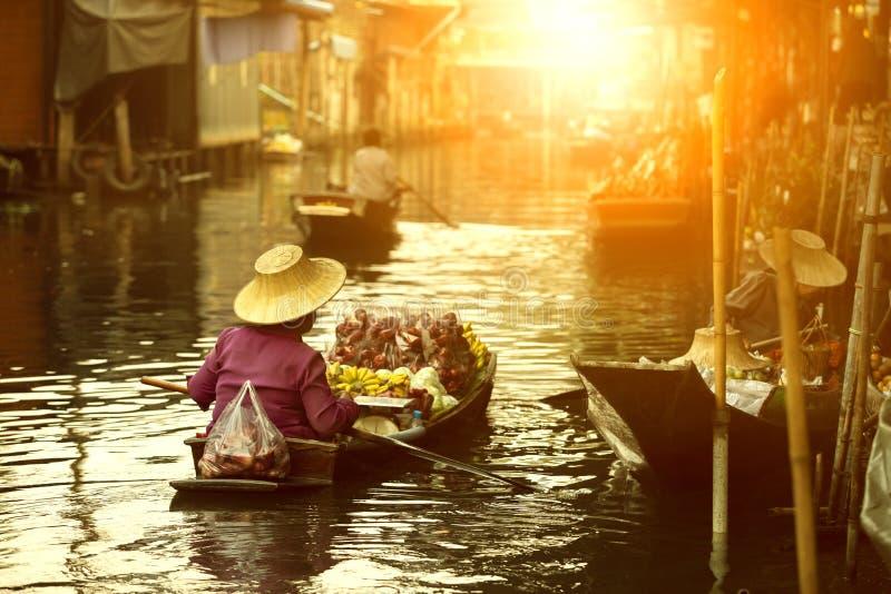 Vendedor tailandés de la fruta que navega el barco de madera en mercado flotante de la tradición de Tailandia foto de archivo