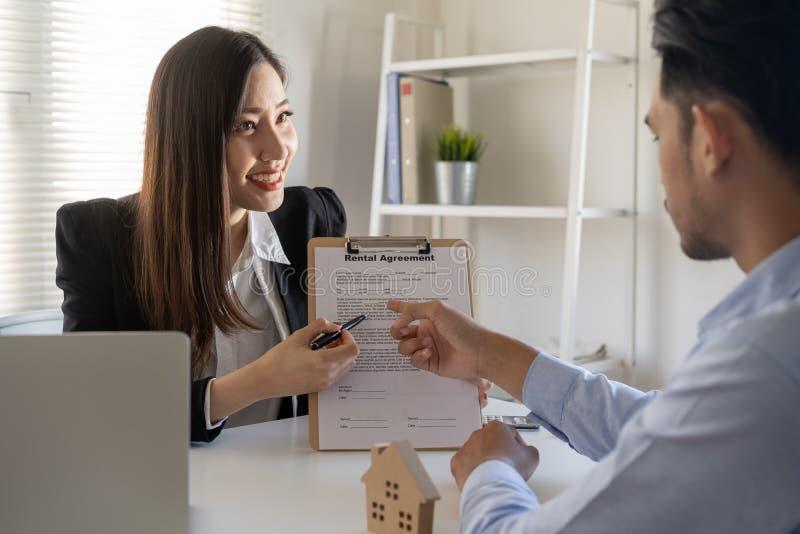 Vendedor una mujer da consejos sobre la compra de una casa para los clientes masculinos en la oficina fotos de archivo