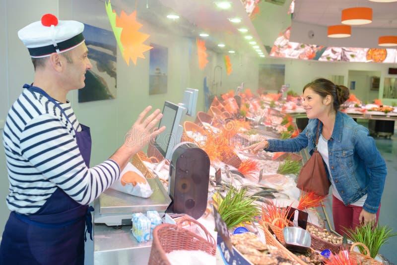 Vendedor y cliente de los mariscos fotos de archivo