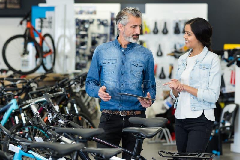 Vendedor y cliente femenino que miran las bicicletas fotos de archivo