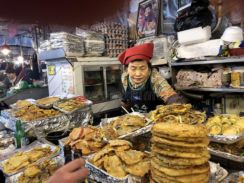 Vendedor y parada de comida en el mercado de Gwangjang, Seúl, Corea foto de archivo libre de regalías
