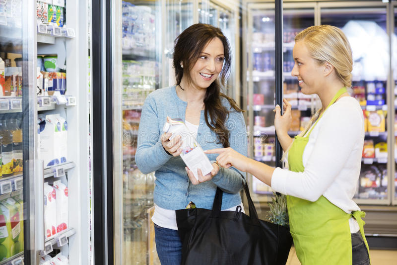 Vendedora Assisting Female Customer para escolher o produto fotografia de stock