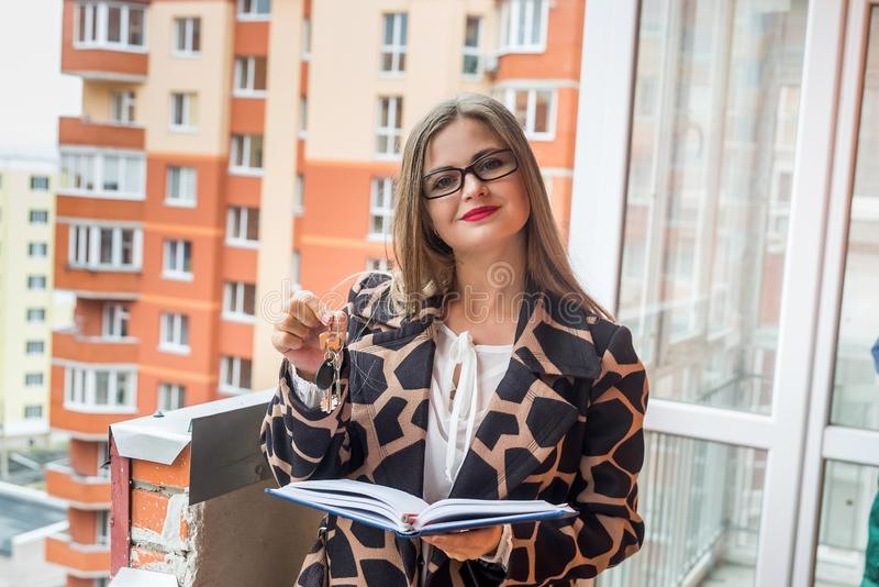Vendedora bonita que mostra chaves do apartamento novo fotos de stock royalty free