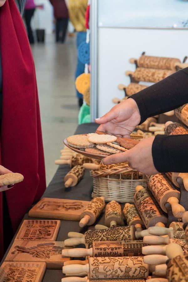 A vendedora dá cookies ao cliente no mercado de domingo fotos de stock