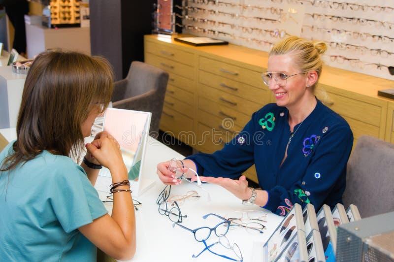 Vendedora do salão de beleza do ótico com seu cliente que escolhe monóculos imagens de stock