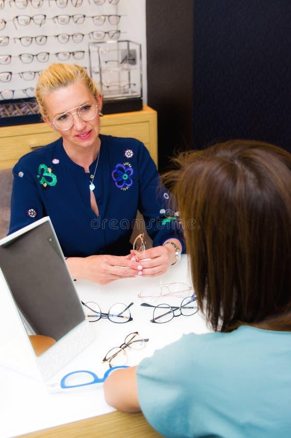 Vendedora do salão de beleza do ótico com seu cliente que escolhe monóculos imagens de stock royalty free