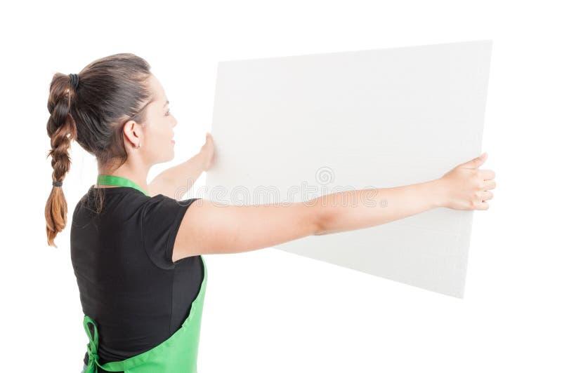 Vendedora nova que guarda o quadro de avisos vazio grande fotografia de stock