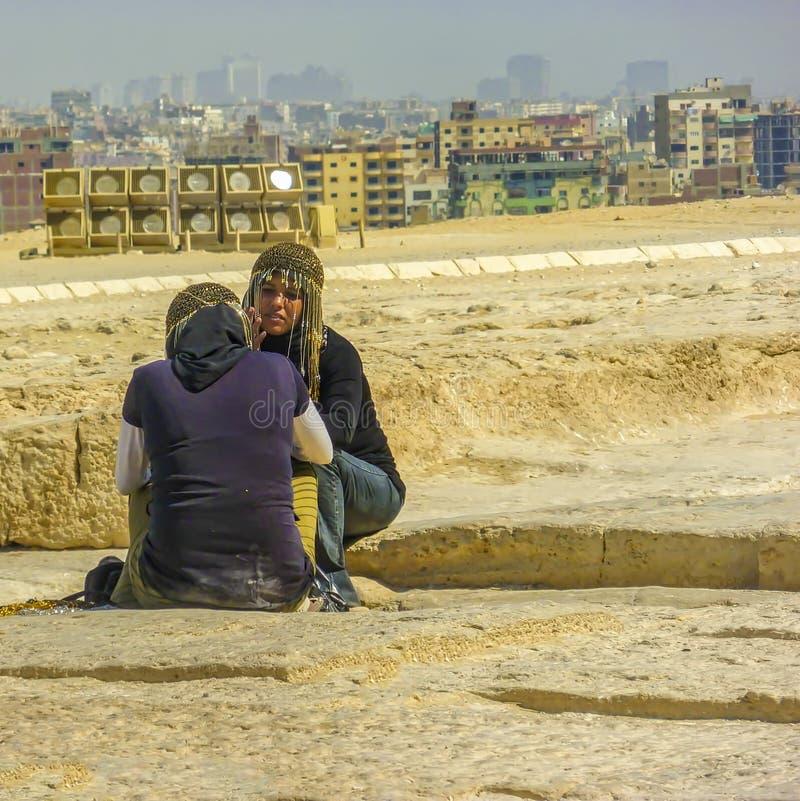 Vendedores egipcios de la pirámide de las mujeres El Cairo en el fondo fotos de archivo