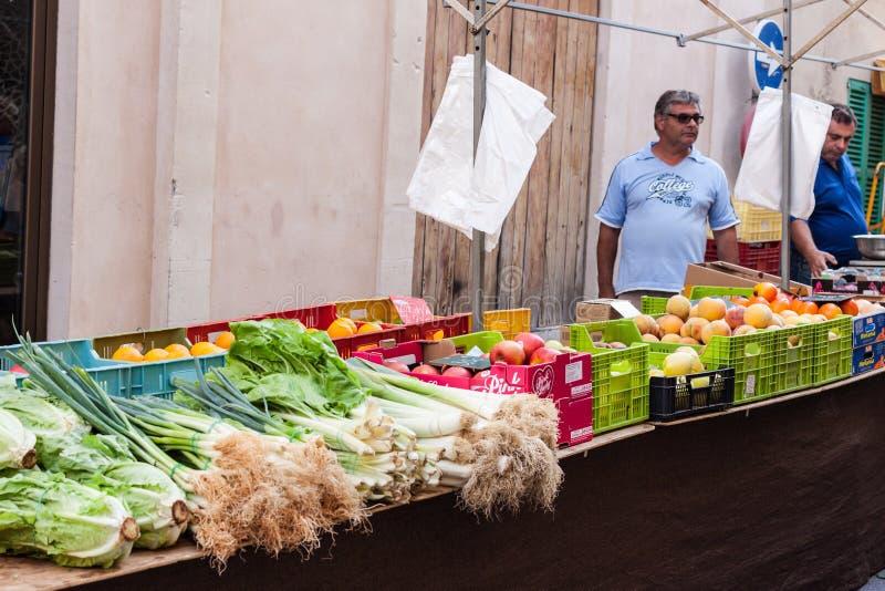Vendedores locales que venden las frutas y verduras en el mercado de Sineu foto de archivo libre de regalías