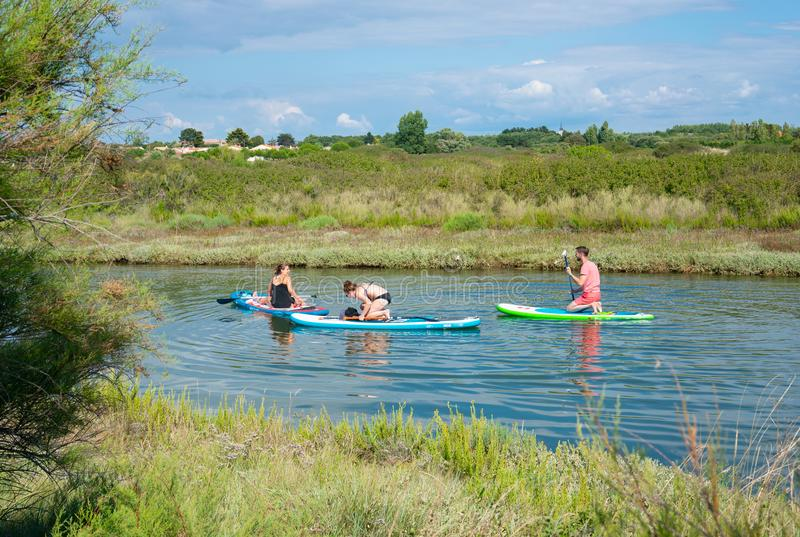 Young people enjoying doing stand up paddle on a calm river on hot summer day stock photos