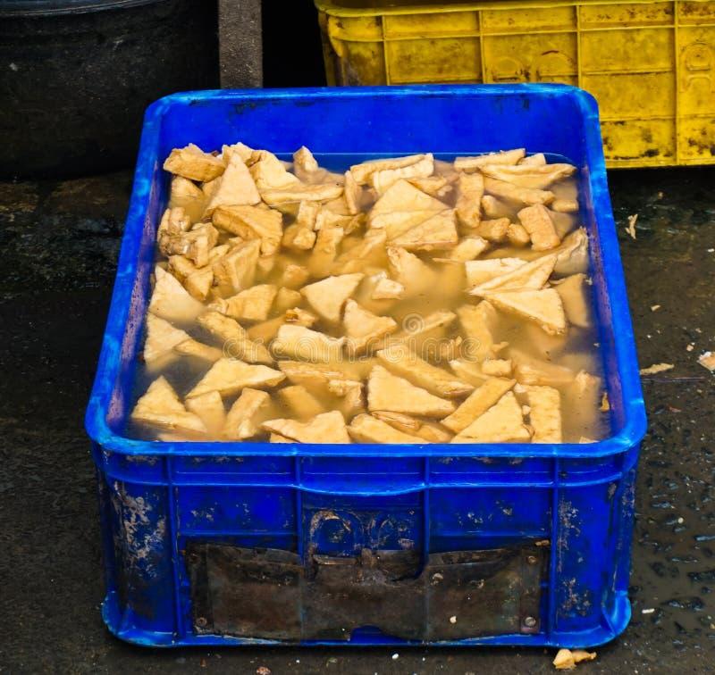 Vendendo o tofu amarelo na cubeta azul Jakarta recolhido foto Indonésia imagem de stock royalty free