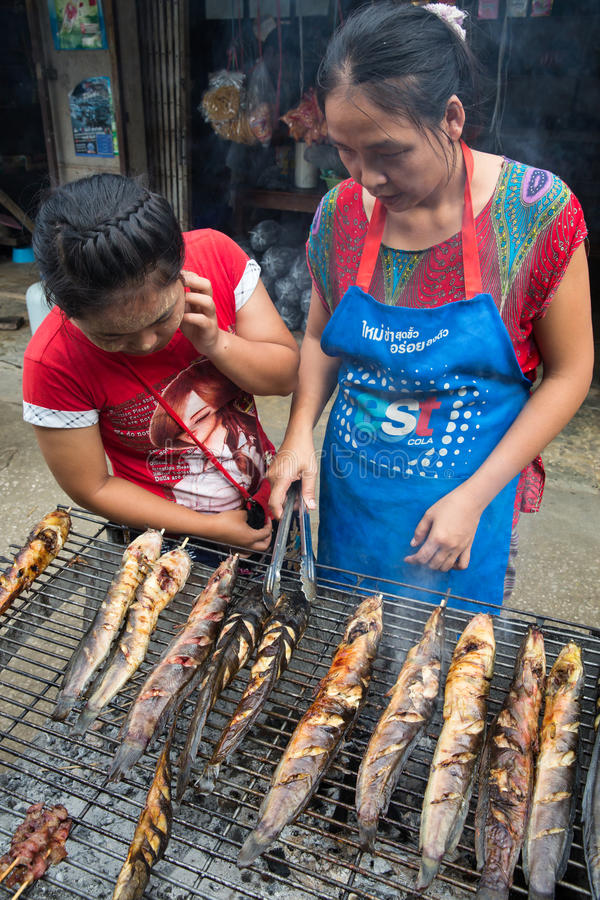 Vender grilling catfish. MAE SOT, THAILAND - OCTOBER7 : Retail vendor on the sidewalk is grilling catfish , choosing and selling for a customer at Mae Sot, Tak royalty free stock images