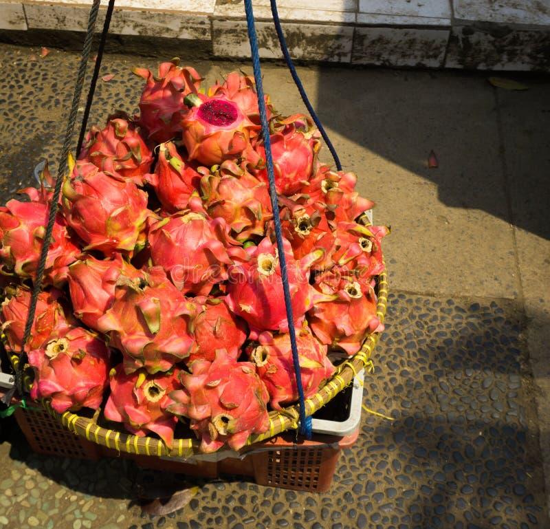Vender o dargon vermelho frutifica em um depok recolhido Indonésia da cesta a foto de bambu imagem de stock