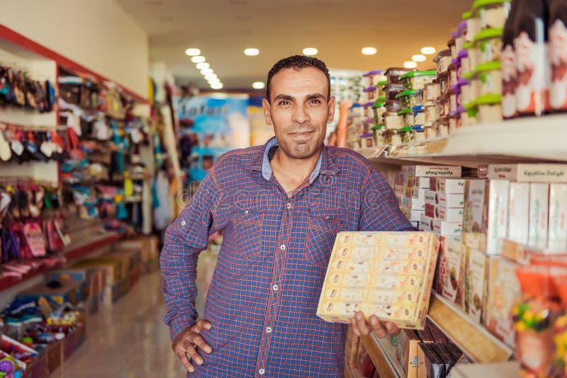 Vendeur égyptien affable montrant des bonbons photos stock