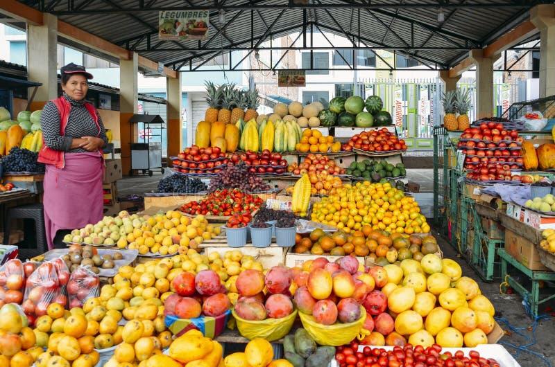 Vendeur équatorien de fruit de femme devant ses affichages des fruits tropicaux sur un marché image stock