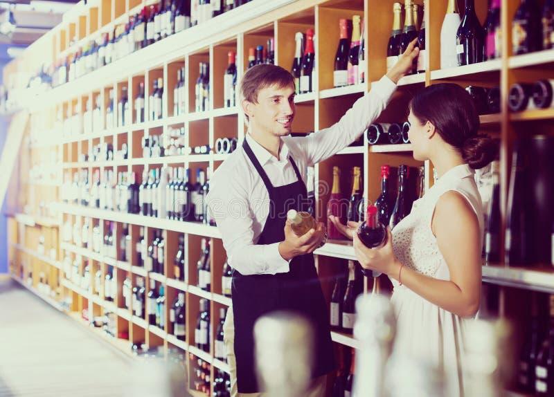 Vendeur aidant à acheter la bouteille images stock
