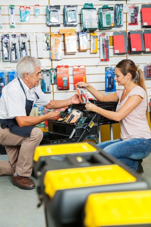 Vendeur Assisting Customer In sélectionnant des outils à photo libre de droits