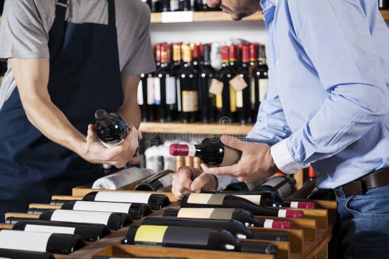 Vendeur Assisting Customer In sélectionnant la bouteille de vin chez Supermar photo stock