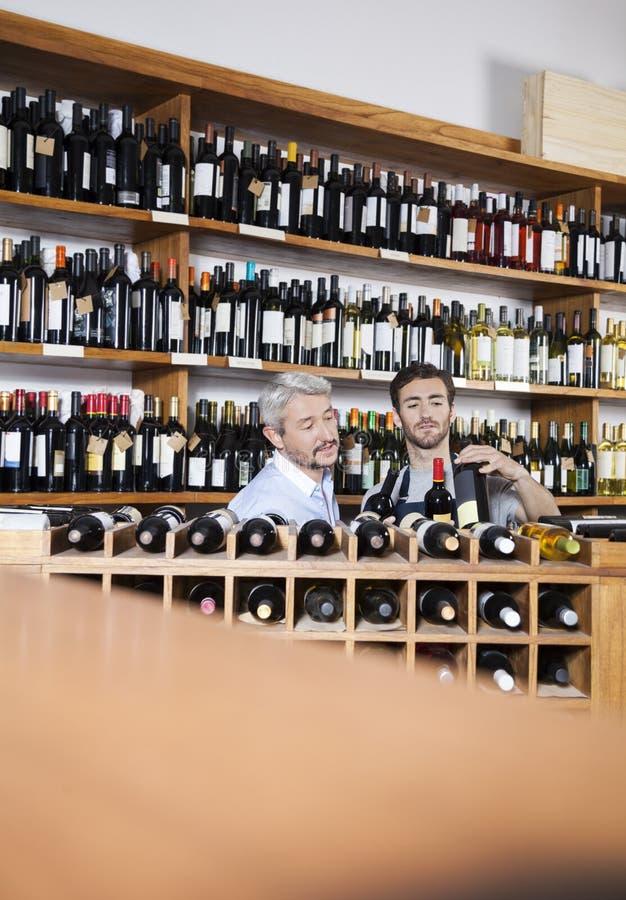 Vendeur Assisting Customer In sélectionnant la bouteille de vin chez Supermar images libres de droits