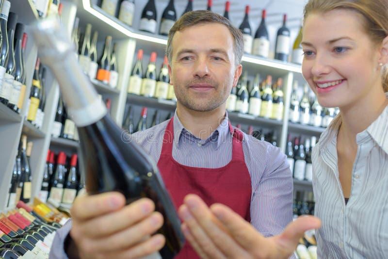 Vendeur Assisting Female Customer en choisissant le vin image libre de droits