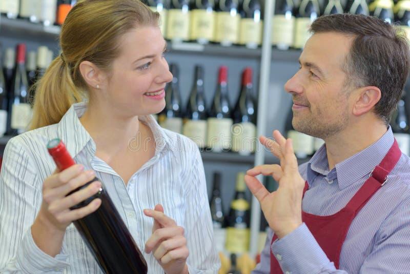 Vendeur Assisting Female Customer en choisissant le vin photo libre de droits