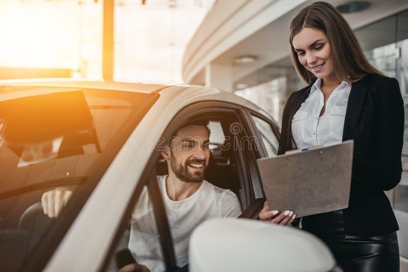 Vendeur avec le client au concessionnaire automobile photographie stock