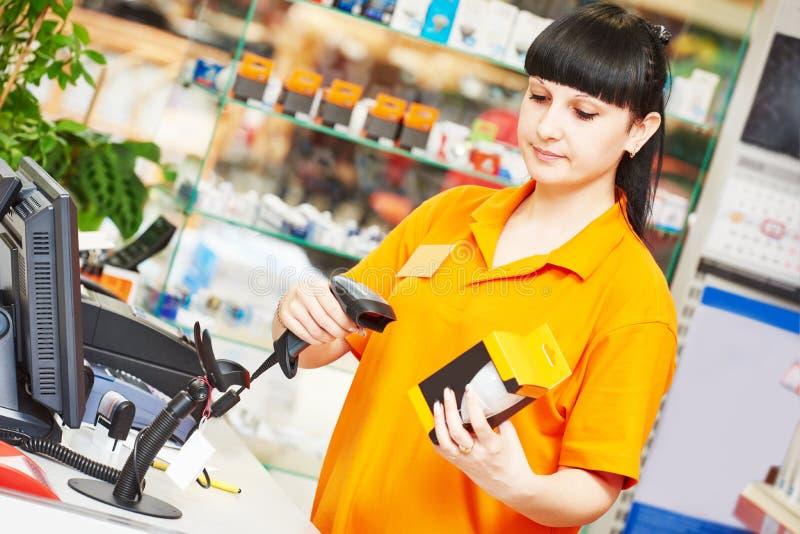 Vendeur avec le scanner de code barres dans la boutique photos stock