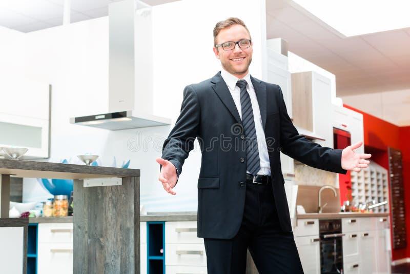 vendeur dans la salle d 39 exposition de meubles de cuisine domestique image stock image 48938993. Black Bedroom Furniture Sets. Home Design Ideas