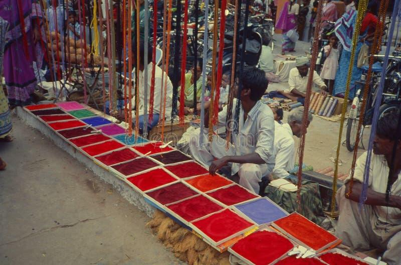 Vendeur de couleur de Rangoli vendant la poudre de couleur sur le marché de dimanche photographie stock