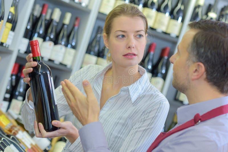Vendeur de femelle adulte montrant le vin de bouteille au client masculin photos stock