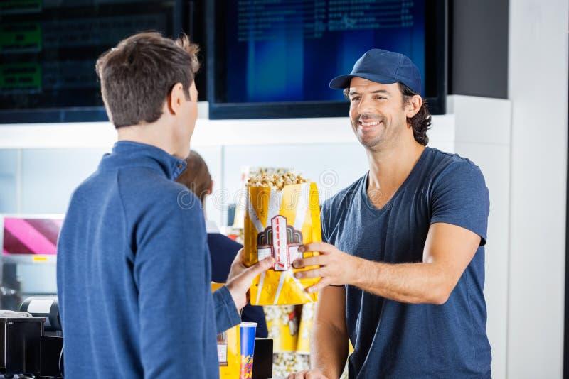 Vendeur de sourire donnant le maïs éclaté à l'homme à la concession images stock