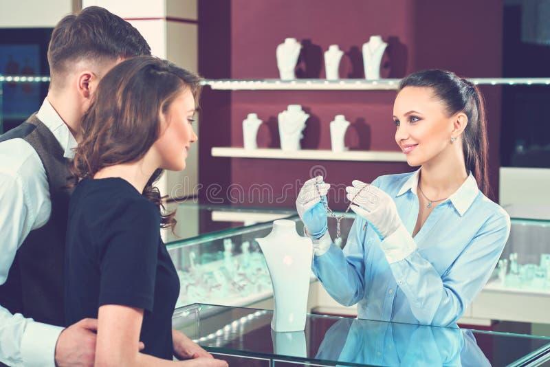 Vendeur de sourire montrant le collier pour des acheteurs au magasin de bijoux images libres de droits