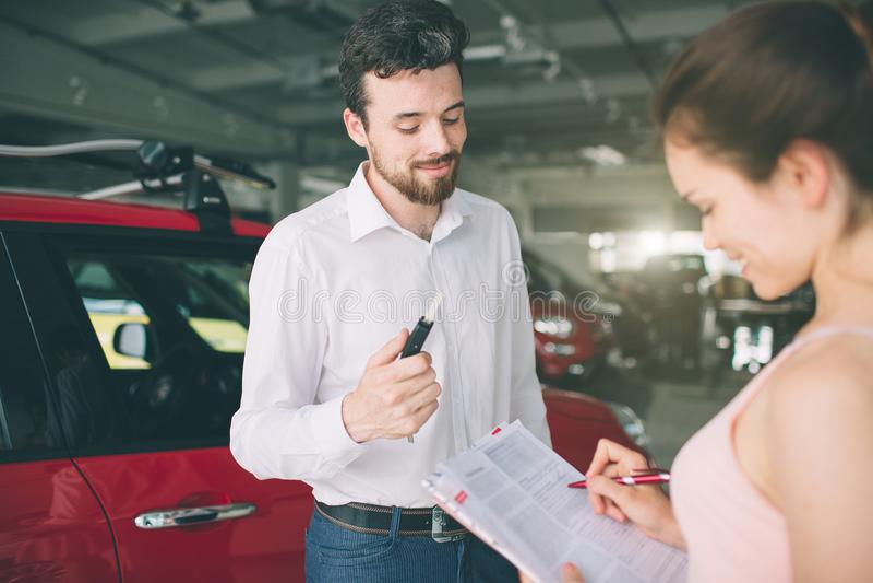 Vendeur de voiture amical parlant à une jeune femme et montrant une nouvelle voiture à l'intérieur de la signature de salle d'exp photos stock