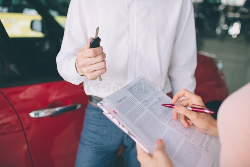 Vendeur de voiture amical parlant à une jeune femme et montrant une nouvelle voiture à l'intérieur de la signature de salle d'exp photo stock