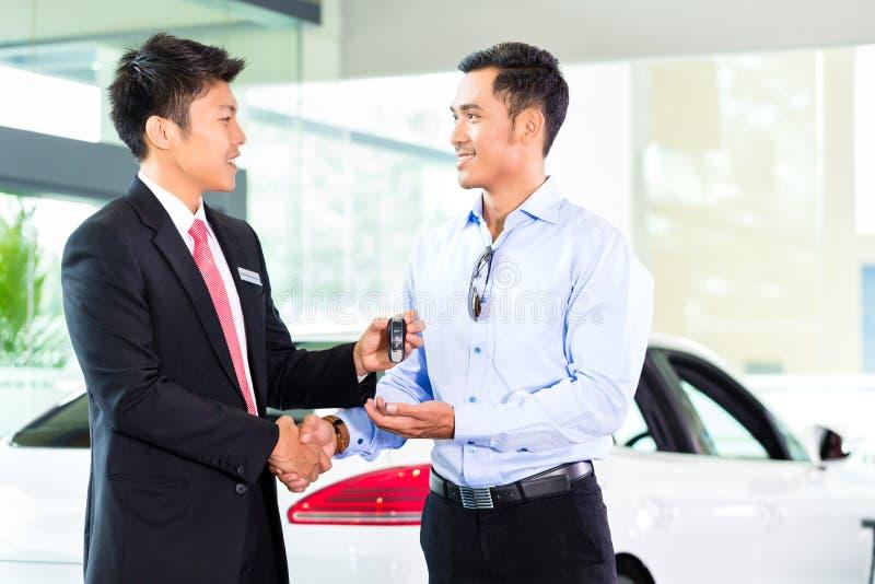 Vendeur de voiture asiatique vendant l'automobile au client images stock