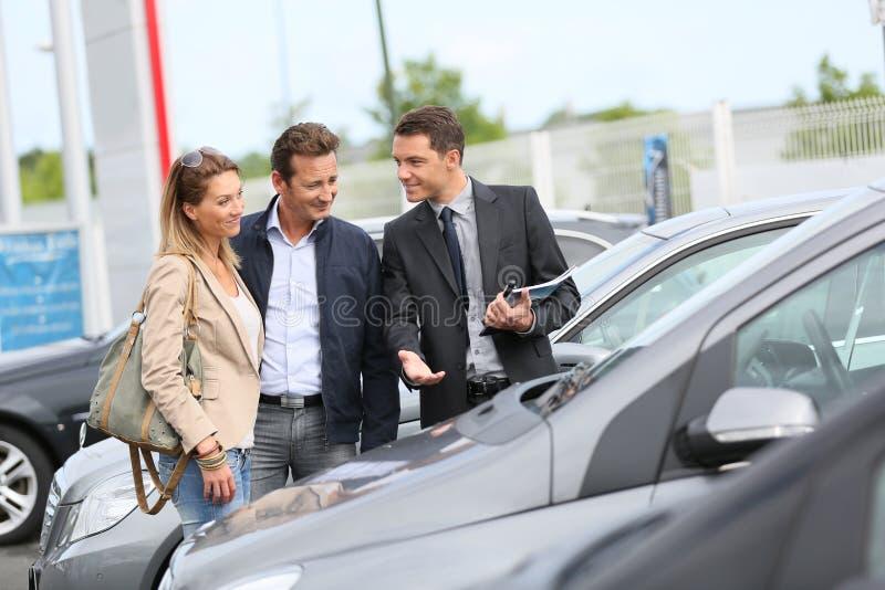 Vendeur de voiture montrant des véhicules aux clients image stock