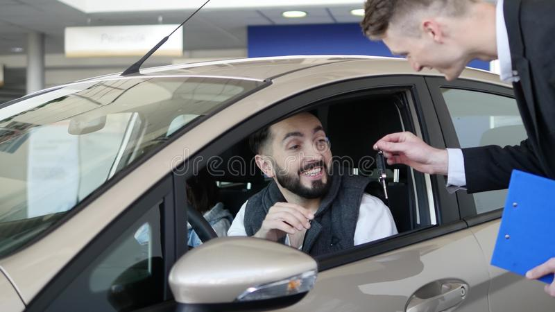 Vendeur de voiture remettant les clés pour une nouvelle voiture image libre de droits