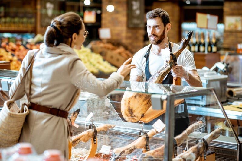 Vendeur et femme avec le jamon dans le supermarché image stock