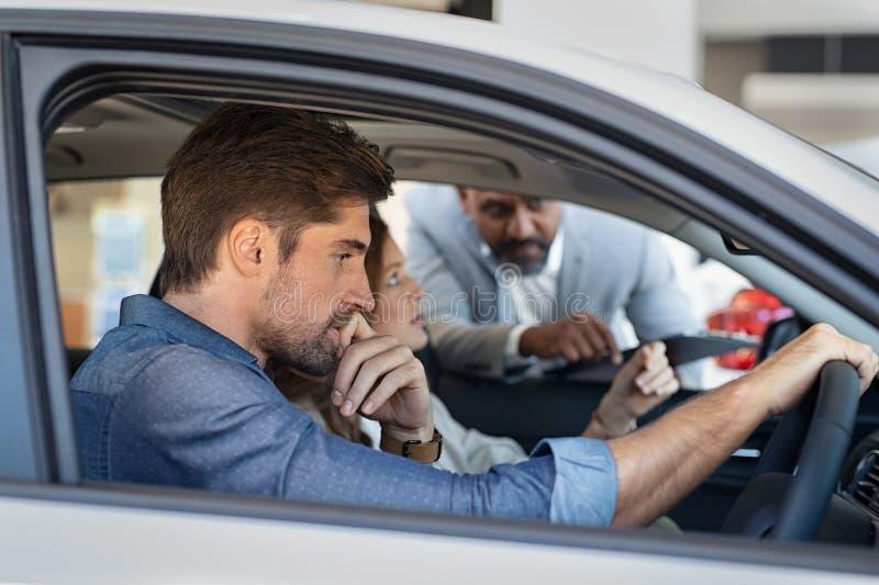 Vendeur expliquant des caractéristiques de voiture photo stock
