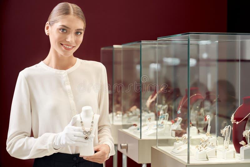 Vendeur féminin attirant montrant le collier de concepteur d'or photographie stock libre de droits